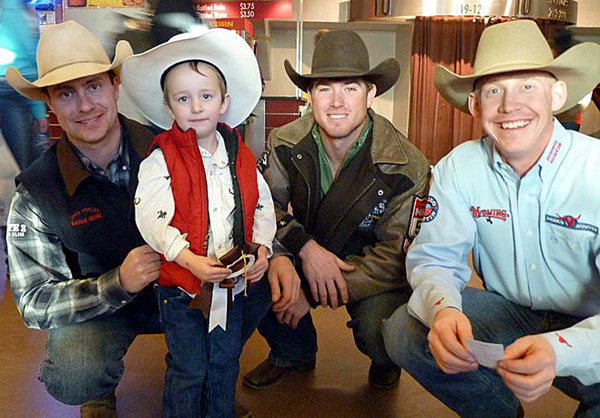 Three-year-old Cade Hemphill poses for a photograph with three of the top saddle bronc riders in ProRodeo, from left, Chad Ferley, Cort Scheer and Chet Johnson.