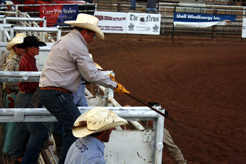 Pete Carr, owner of the livestock firm Carr Pro Rodeo, hangs on to the flank during bareback riding Thursday.