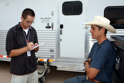 Hobbs News-Sun reporter Lance Crenshaw, left, interviews heeling world champion Patrick Smith before Wednesday's first performance of the Lea County Fair and Rodeo in Lovington. Crenshaw wrote a story on 14-time world champion Trevor Brazile that appeared in Thursday's edition.