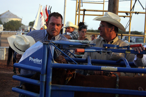 Shane Henderson, left, of Winfield, Kan., speaks with chute boss John Gwatney as they wait on another bulldogger to make his run Thursday.