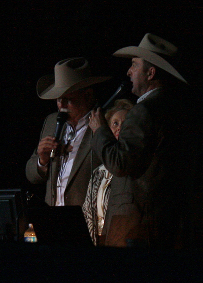 Announcers Charlie Throckmorton, left, and Justin McKee, right, visit with Donna McSpadden, wife of the late Clem McSpadden, in the opening of the second night of the Clem McSpadden National Finals Steer Roping.