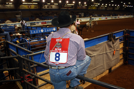 Chet Herren of Pawhuska, Okla., watches the action from a perch along the fence behind the roping chute on Friday night.