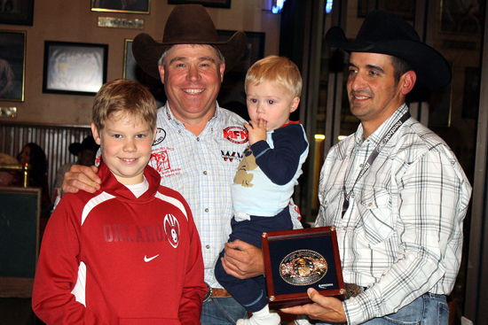 Robert Simpson presents J.P. Wickett and his sons with J.P.'s Montana Silversmiths Go-Round Buckle for his fourth-round win.