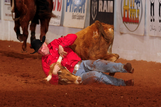K.C. Jones tumbles with his bulldogging steer on Sunday afternoon, posting a 28.5-second run. While it wasn't his fastest of the five-round Timed Event Championship, it helped the Wyoming cowboy clinch his fifth Timed Event Title. (PHOTO BY JAMES PHIFER)