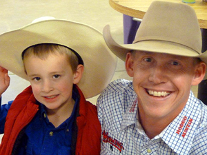 Cade Hemphill and Chet Johnson smile for a shot during the Denver rodeo in January. A hero and his cowboy meet again. (PHOTO BY KARLA HEMPHILL)