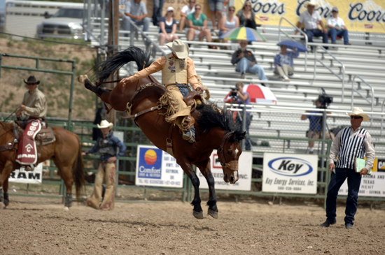 Chad Ferley, the 2006 world champion saddle bronc rider, matches moves with Frontier Rodeo's Griz during the second performance of the Guymon (Okla.) Pioneer Days Rodeo on Sunday afternoon. He leads the bronc riding with an 87. (ROBBY FREEMAN PHOTO)