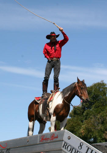 John Payne cracks his whip while standing atop his horse that stands on top of his trailer in the rodeo arena. He will be one of the featured acts at Dodge City (Kan.) Roundup Rodeo, set for 7:45 p.m. Aug. 1-5.