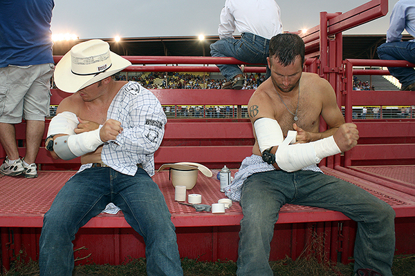 Bareback riders Steven Peebles, left, and Brian Bain, both Wrangler National Finals Rodeo qualifiers who are in the top 15 this season, tape their riding arms in preparation for Friday night's rides at the Dodge City Roundup Rodeo.
