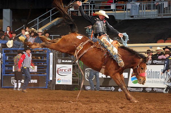 Taos Muncy rides Carr Pro Rodeo's Mike & Ike for 85 points to take the lead in the first round of the Ram National Circuit Finals Rodeo in Oklahoma City. (JAMES PHIFER PHOTO)