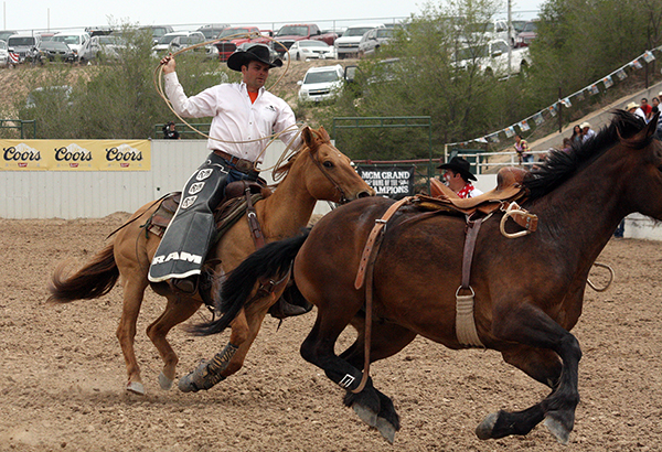 Jeremy Hight, a pickup man for Carr Pro Rodeo and Pete Carr's Classic Pro Rodeo, tries to wrangle a saddle bronc in Guymon, Okla., the first weekend in May 2013. (LYNETTE HARBIN PHOTO)