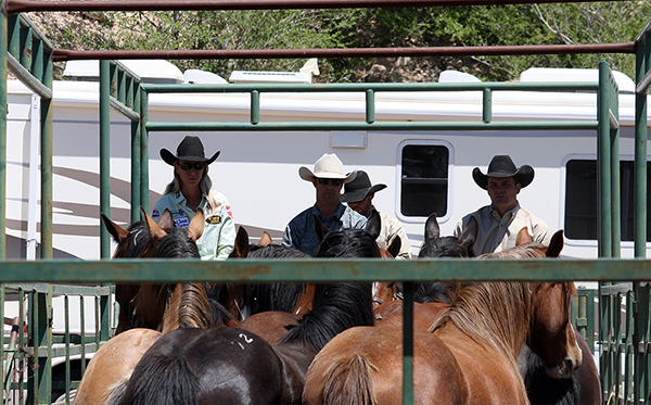 World champions Sherry Cevi, left, and Chad Ferley, center, wait with Carr pickup man Jeremy Hight prior to the opening in Guymon. Production is a big part of the experience at a Carr rodeo.