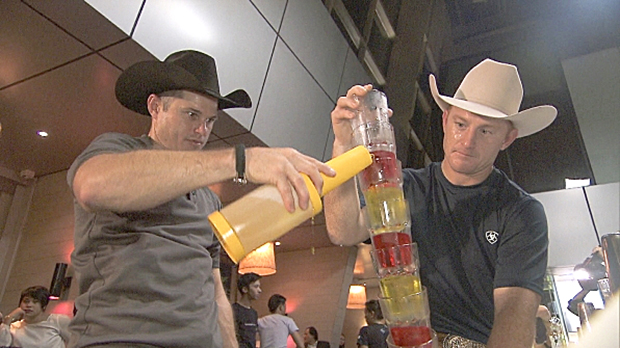 Cowboy brothers Cord, left, and Jet McCoy must mix seven cocktails and pour them simultaneously into a pyramid of glasses. Once the cocktails were made properly, they delivered them across a pool to receive the next clue Sunday, March 16, on Season 24 of The Amazing Race. (CBS PHOTO)