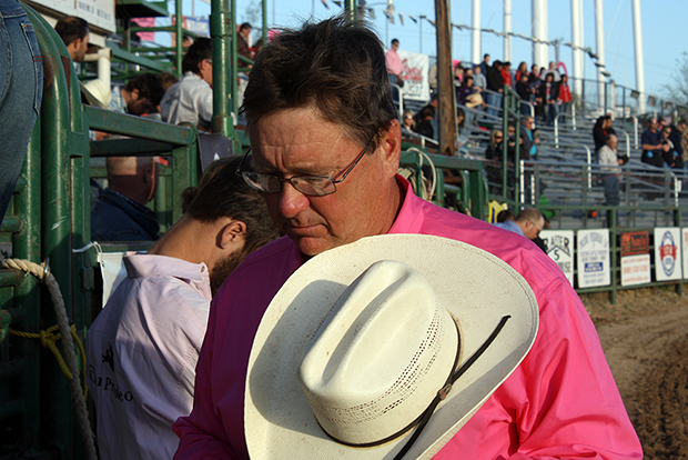 John Gwatney bows his head in prayer prior to a recent rodeo performance. Gwatney and his wife, Sandy, are a big part of the Pete Carr Pro Rodeo family.