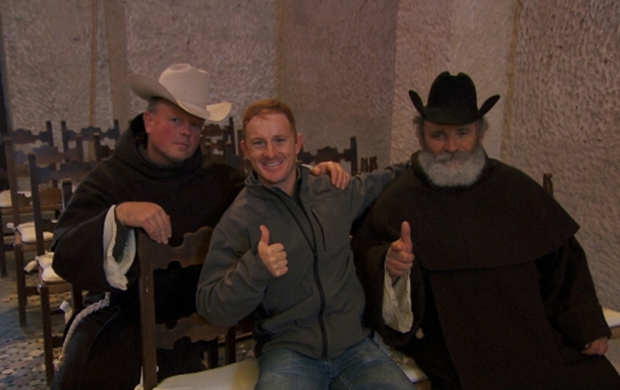 "Cord McCoy poses with two monks wearing cowboy hats at La Badia Monastery while his brother, Jet, completes the Road Block during the eighth leg of ""The Amazing Race"" All-Star Edition, which aired Sunday, April 20. (CBS PHOTO)"
