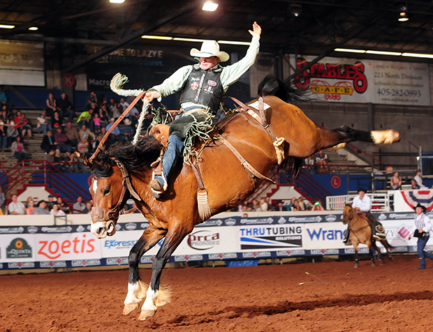 Jacobs Crawley rides J Bar J Rodeo's Sweatin Bullets for 83 points to share the final-round title at the Ram National Circuit Finals Rodeo on Saturday night at the Lazy E Arena. He was crowned the national champion. (PRCA PRORODEO PHOTO BY JAMES PHIFER)