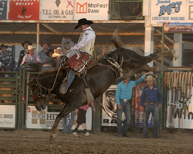 Chet Johnson rides Pete Carr's Classic Pro Rodeo's Sweet Maria for 84 points on Friday night to share the saddle bronc riding lead at the Guymon Pioneer Days Rodeo. (ROBBY FREEMAN PHOTO)