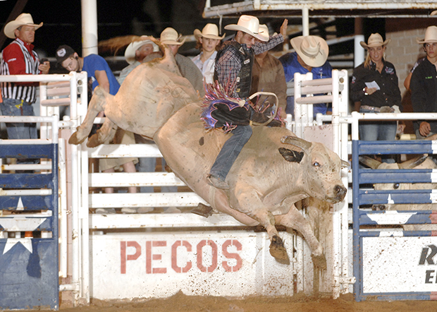 Elliot Jacoby, a 2013 Wrangler National Finals Rodeo qualifier from Fredricksburg, Texas, rides Pete Carr's Classic Pro Rodeo's Hustler for 91 points to win the 2013 West of the Pecos bull riding title. He will return to Pecos, Texas, next week to defend his championship. (ROBBY FREEMAN PHOTO)