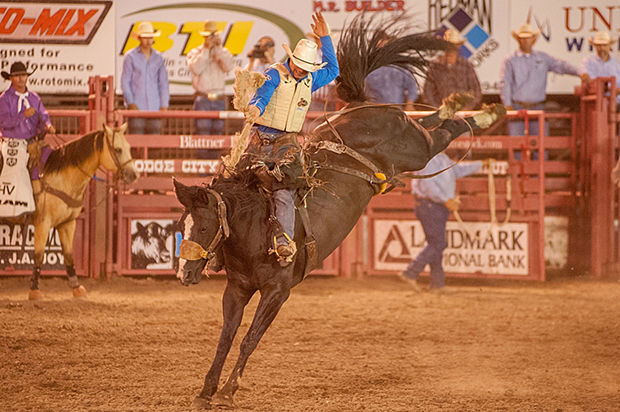 Heith DeMoss rides Frontier Rodeo's Midnight Delight for 87 points Friday night to share the first-round lead in the bronc riding at Dodge City Roundup Rodeo. (FRAN RUCHALSKI PHOTO)