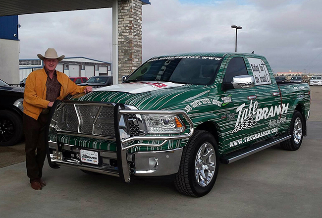 "Roy Cooper poses with his wrapped Tate Branch Auto Group pickup he will use as he travels the country with rodeo and by ""Riding for the Brand"" during his appearances and while commentating on Ride TV."