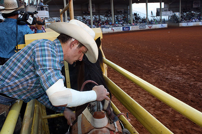 Bareback rider Bill Tutor adjusts his riggin' on Pete Carr Pro Rodeo's Dirty Jacket during the 2014 Lea County Fair and Rodeo.