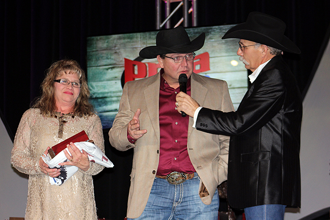 Will Rogers Stampede chairman David Petty, center, talks about the Claremore rodeo with emcee Doug Mathis during Wednesday's PRCA awards banquet in Las Vegas. Petty is on stage with his wife and another member of the committee, Dawn Petty.