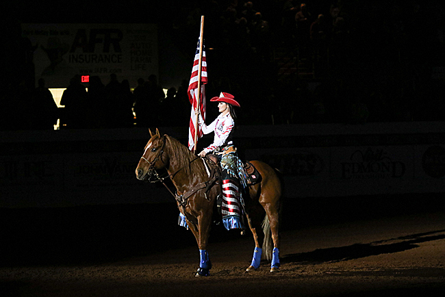 Elise Wade holds Old Glory during the national anthem. (PHOTO BY STEPHANIE COOMBES)