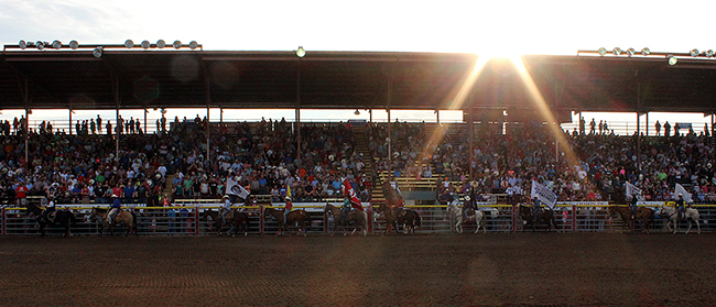 The grand entry parades in front of a pack grandstands during one of the performances of the 2015 Dodge City Roundup Rodeo. The annual event celebrates its 40th year in 2016.