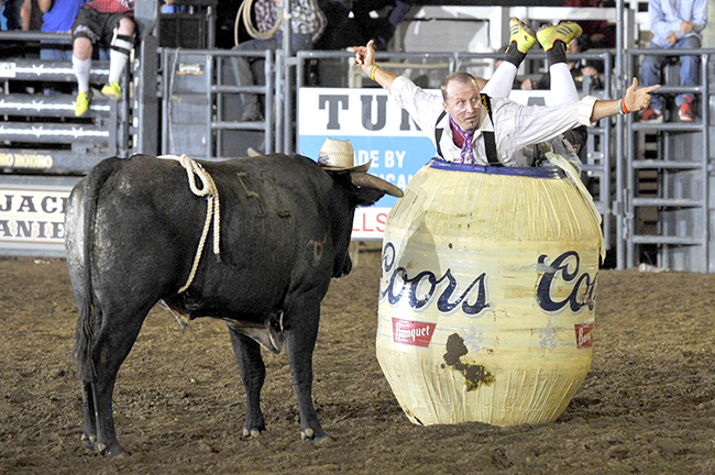 Ross Hill shows the crowd that he has placed his cowboy hat on the head of his bull, AK-47, during Saturday's Bullfighters Only tour event in Gooding, Idaho. Hill won the event with an 89.5-point fight in the final round. (W.T. BRUCE PHOTO)
