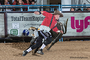 Tate Rhoads battles his bull during Friday's qualifier round. (TODD BREWER PHOTO)