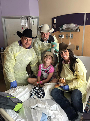 Representatives for Cowboys Who Care, including Pete Carr on the left, deliver a cowboy hat to a young patient. (COURTESY PHOTO)