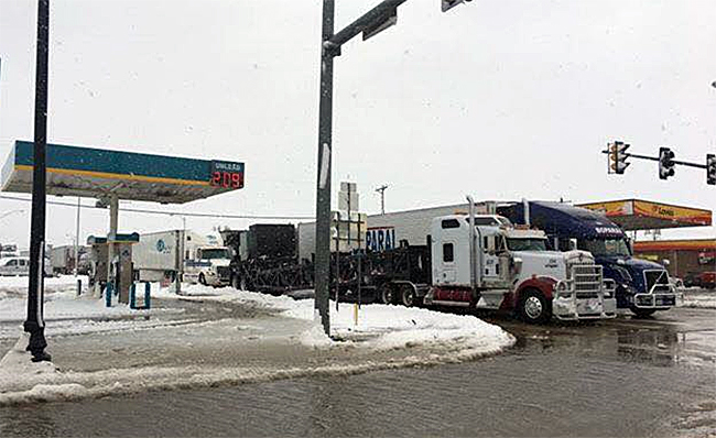 Semi tractor-trailers line up on U.S. Highway 54 at the Main Street stoplight as westbound traffic on the highway is stalled in Guymon, Okla., on Sunday afternoon. The weather and traffic conditions have delayed the start of competition at Pioneer Days Rodeo. Monday's steer roping is postponed and will begin at 9 a.m. Tuesday (PHOTO COURTESY OF THE GUYMON DAILY HERALD)