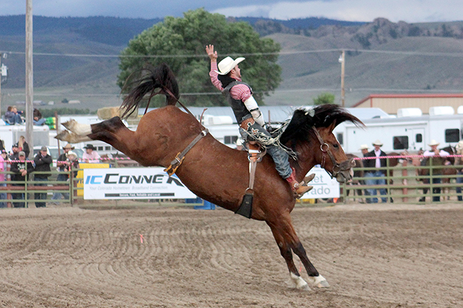 Kash Wilson rides Three Hills Rodeo's Big Show for 86 points Thursday night to take the lead at the Cattlemen's Days PRCA Rodeo in Gunnison, Colo.