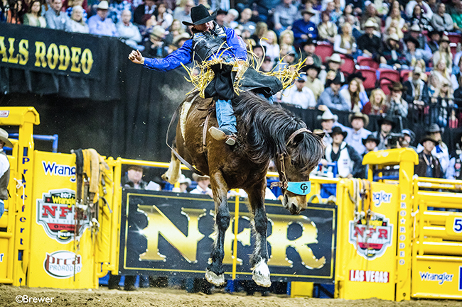 Tanner Aus spurs Pickett Pro Rodeo's Scarlet Fever for 87.5 points to share the second-round victory Friday at the Wrangler National Finals Rodeo. (TODD BREWER PHOTO)