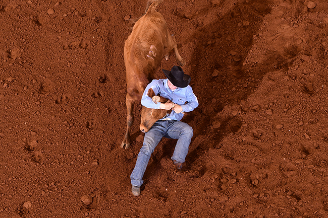 Jordan Ketscher slides with his animal during his 6.8-second steer wrestling run. He won the third go-round of the CINCH Timed Event Championship with a 56.0-second round and also moved into the 15-run aggregate lead. (JAMES PHIFER PHOTO)