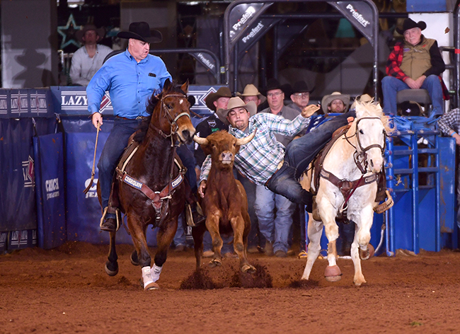 Eric Rogers transitions to his bulldogging steer en route to a 4.3-second run, which helped him to a second-round winning 55.-second go-round during Friday night's performance of the CINCH Timed Event Championship. (JAMES PHIFER PHOTO)