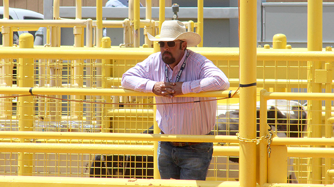 Lea County Fair Board member Trey Kerby, the chairman of the rodeo committee, looks over the competition while performing various duties for the Lea County Fair and Rodeo.