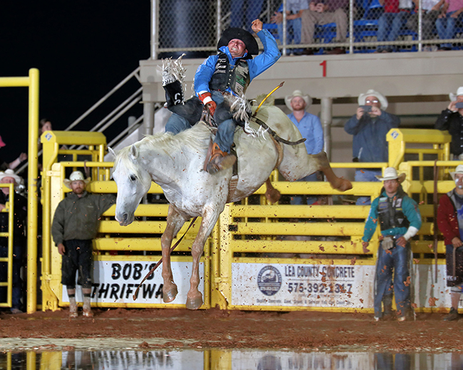 Steven Dent rides Pete Carr Pro Rodeo's Hired Gun through the mud and muck for 87 points Friday night to take the bareback riding at the Lea County Fair and Rodeo. (PHOTO BY PEGGY GANDER)